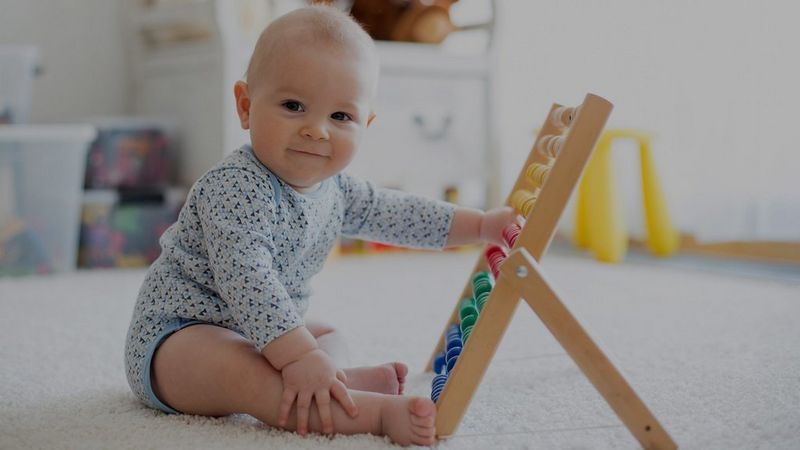 A baby sits upright, playing with coloured beads on an abacus.